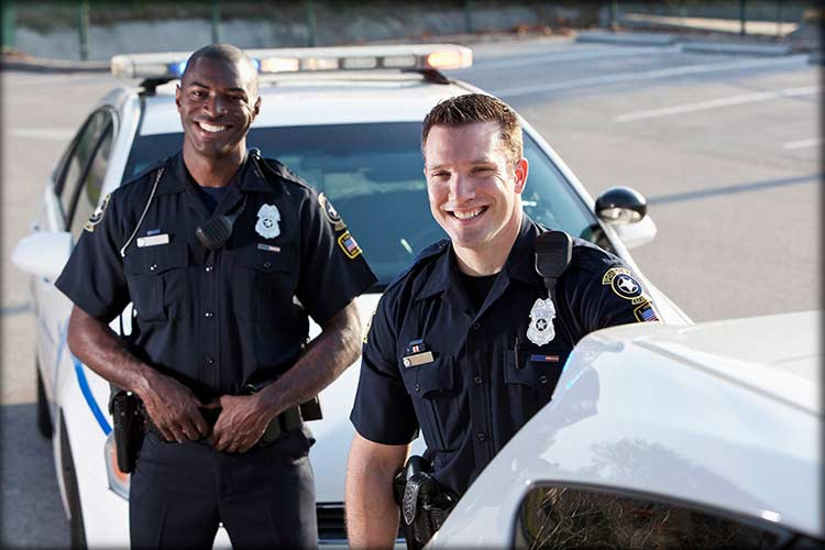 Police officers smiling as they pose by their police cars
