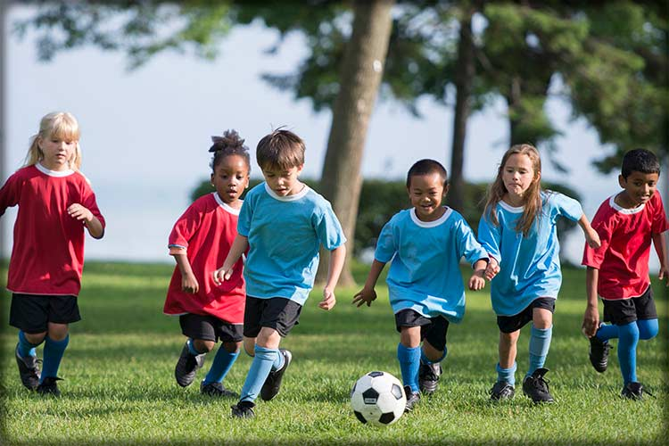 A group of kids playing in a soccer match