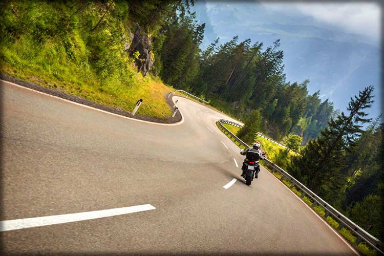Photo of person riding motorcycle on a windy road